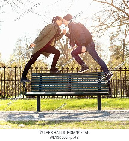 Dating young couple standing on park bench, holding hands