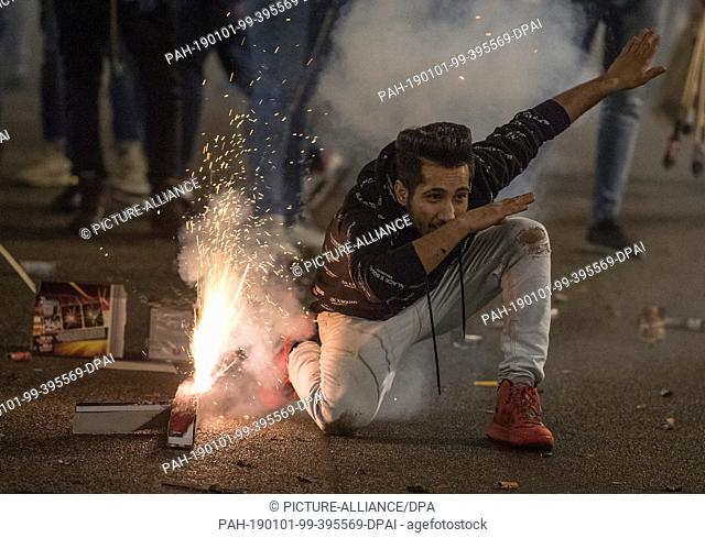 01 January 2019, Hessen, Frankfurt/Main: A man is dancing next to burning fireworks. Thousands of people celebrated the turn of the year in the city centre