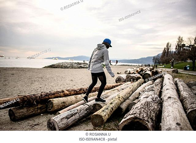 Young woman walking on logs, rear view, English bay, Vancouver, Canada
