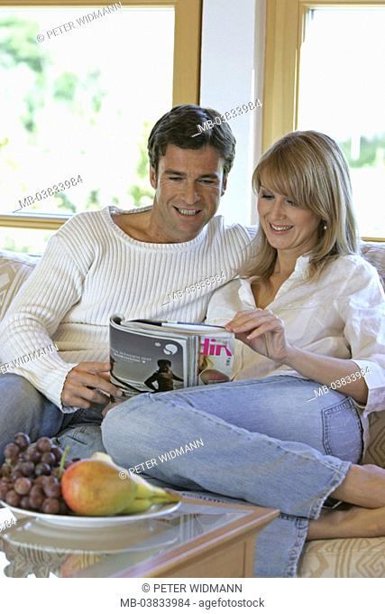 Living rooms, sofa, couple, smiling,  Magazine, reading, together,   Series, 30-40 years, partnership, relationship, marriage, harmony, leisure time