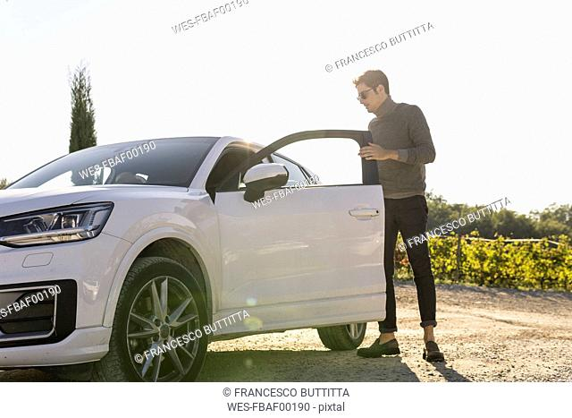 Italy, Tuscany, Siena, young man getting out of car in a vineyard