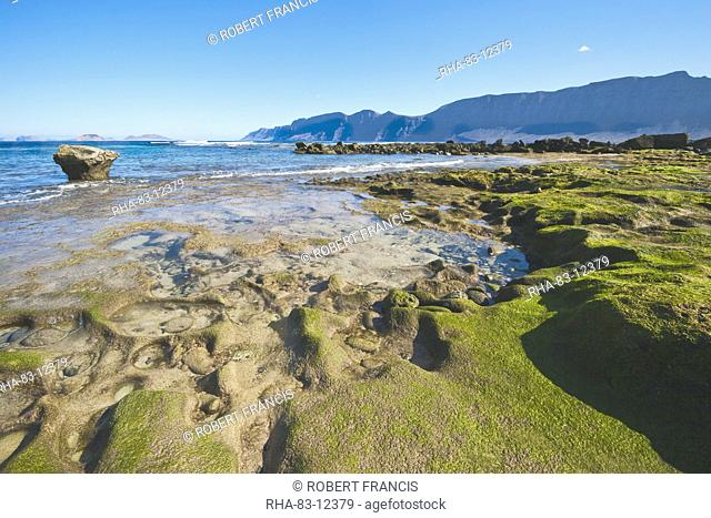 Spectacular 600m volcanic cliffs of the Risco de Famara and Graciosa Island backdrop to the rocky southern shore of the bay at Famara in the north west