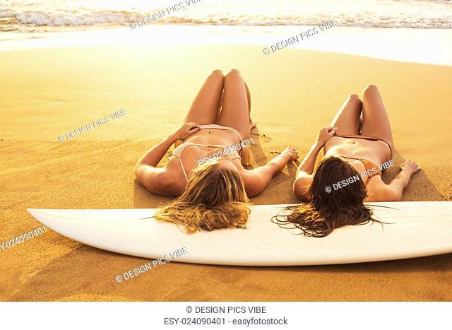 Beautiful Surfer Girls on the Beach at Sunset