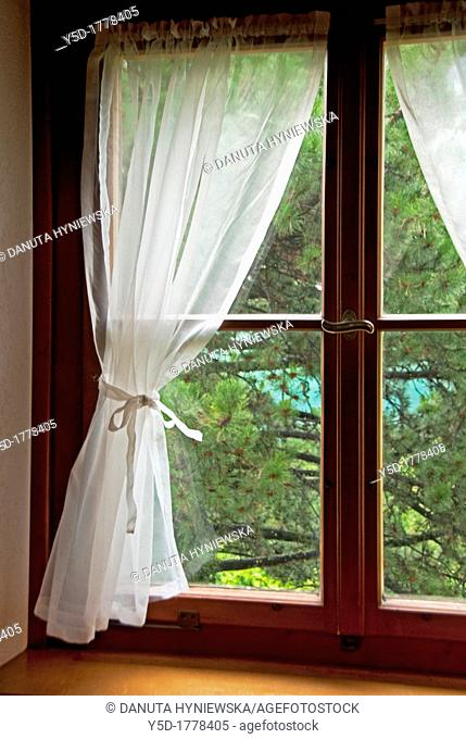 Window with curtain in a residential building seen from interior, symbol of privacy at home