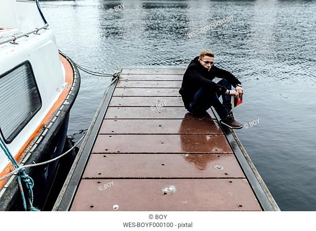 Young man with book cowering on a jetty in winter