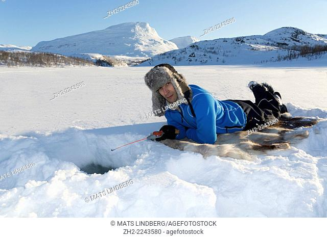 White man, 40-45 years old, icefishing, lying on a reindeer fur in Kiruna, Riksgränsen, Swedish lapland
