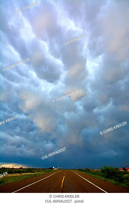 Diminishing perspective of open road and mammatus clouds after storms, near Tucumcari, New Mexico, USA