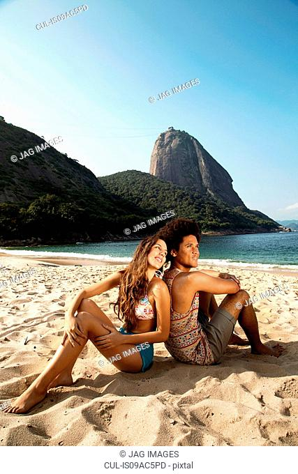 Couple relaxing on beach, Rio de Janeiro, Brazil