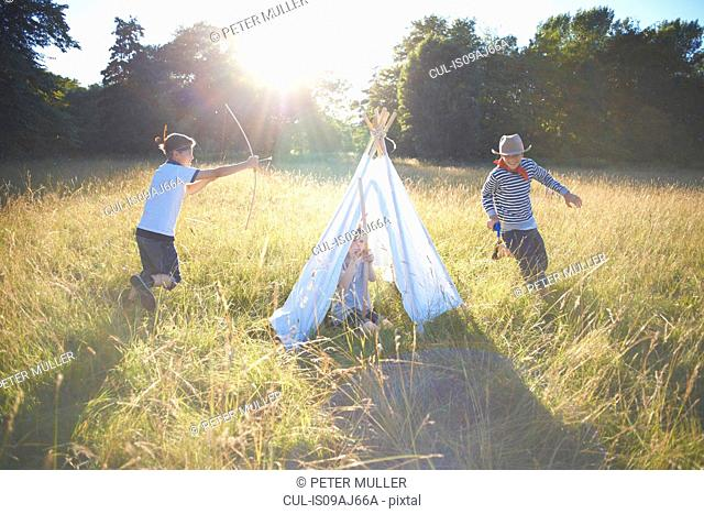 Small group of young boys playing around teepee