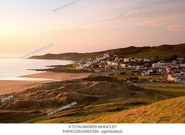 View of coastline and seaside resort at sunset, with Morte Point in distance, viewed from Potters Hill, Woolacombe, North Devon, England, April