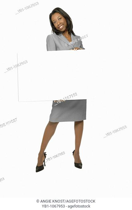 Attractive woman of African ethnicity, holding a blank sign or whiteboard