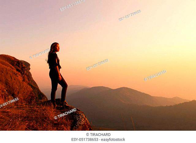 Hipster young girl with backpack enjoying sunset on peak of foggy mountain. Tourist traveler on background view mockup. Hiker looking sunlight in trip in...