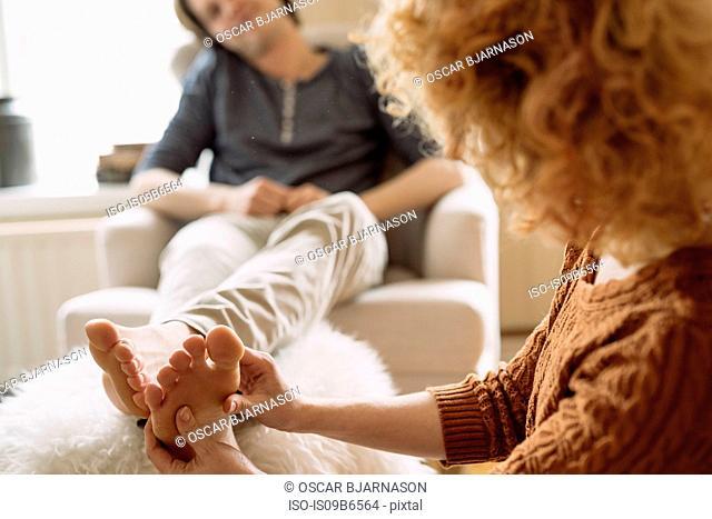 Woman giving man foot massage