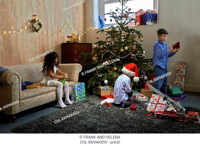 Girl and two brothers opening christmas gifts in sitting room
