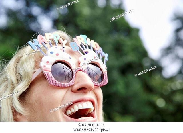 Happy woman wearing birthday eyeglasses