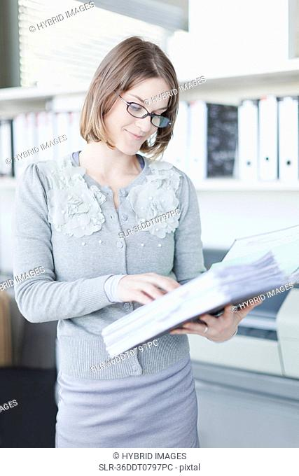 Businesswoman reading book in office