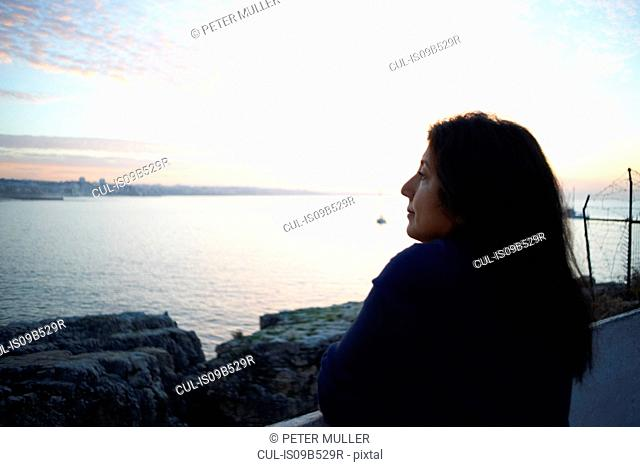 Mature woman gazing out to sea at dusk, Sintra, Portugal