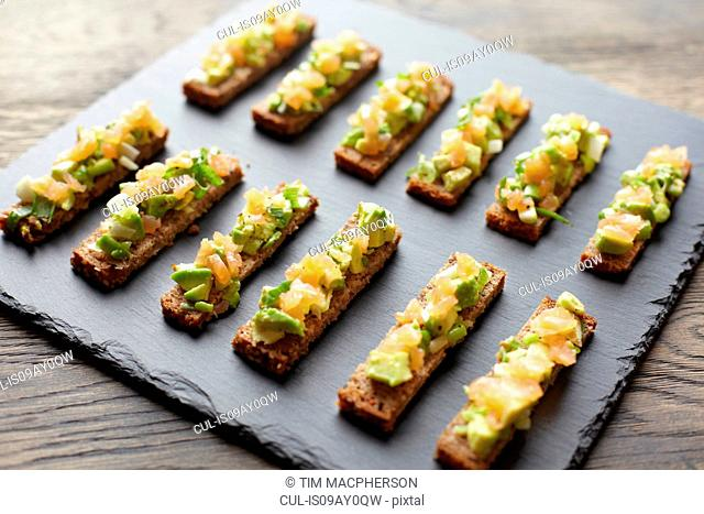 Guacamole, smoked salmon and rye bread canapes