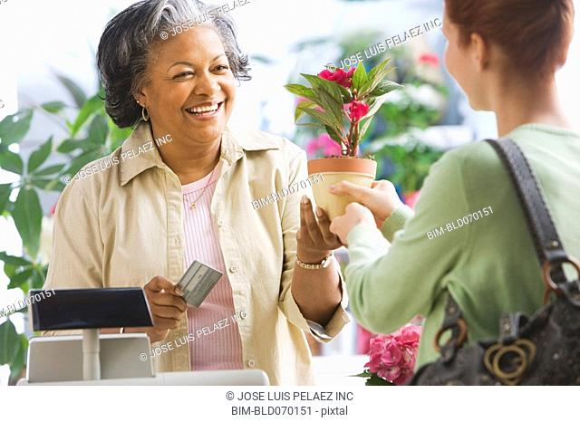 African woman helping customer in florist shop