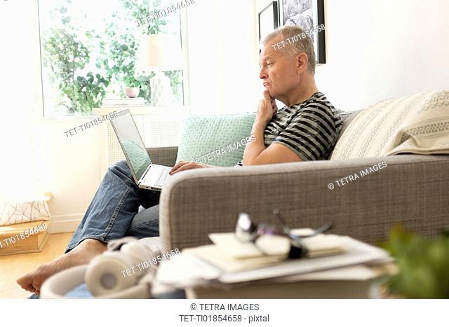 Man sitting on sofa using laptop