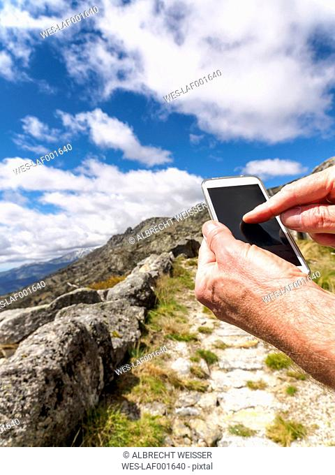 Spain, Sierra de Gredos, hiker with cell phone on trail