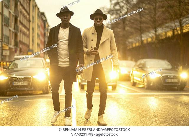 streetstyle, two men walking in the middle of the street in front of cars at night, lights, traffic, evening, Munich, Germany