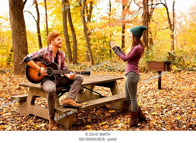 Young woman photographing guitar playing boyfriend in autumn forest