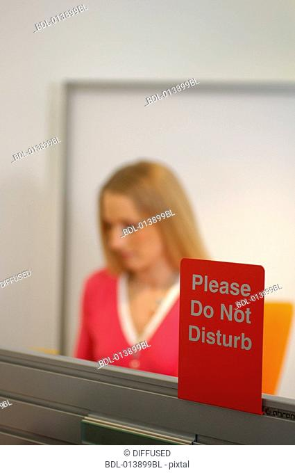 Do not disturb sign with female executive in background