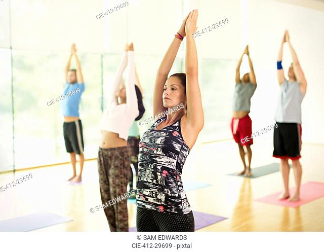 Yoga class with arms raised