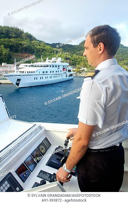 The captain maneuvering the luxury 30 cabins yacht 'Tia Moana' entering Utiroa harbour. Raiatea harbour. Leeward islands. French Polynesia
