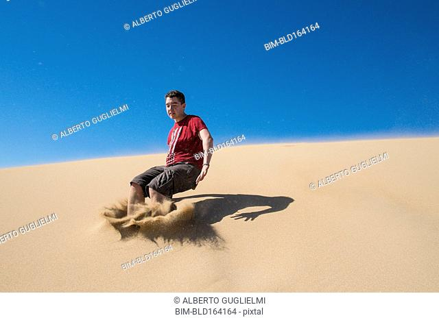 Caucasian teenage boy jumping on sand dune