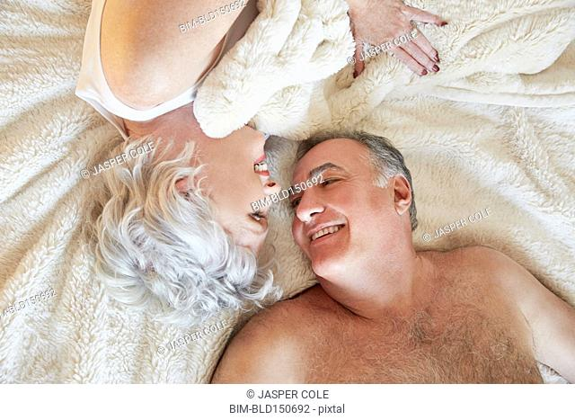 Older couple smiling at each other in bed