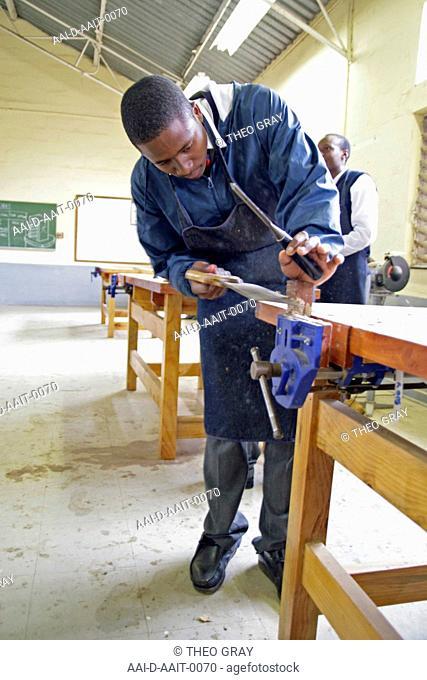 School boy sawing in woodwork classroom, St Mark's School, Mbabane, Hhohho, Kingdom of Swaziland