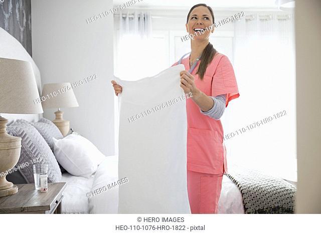 Home nurse making patients bed