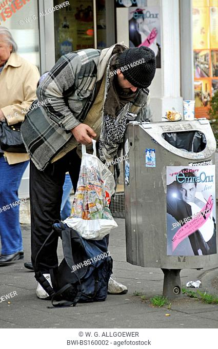 homeless person searching a trashcan, Germany, North Rhine-Westphalia, Cologne