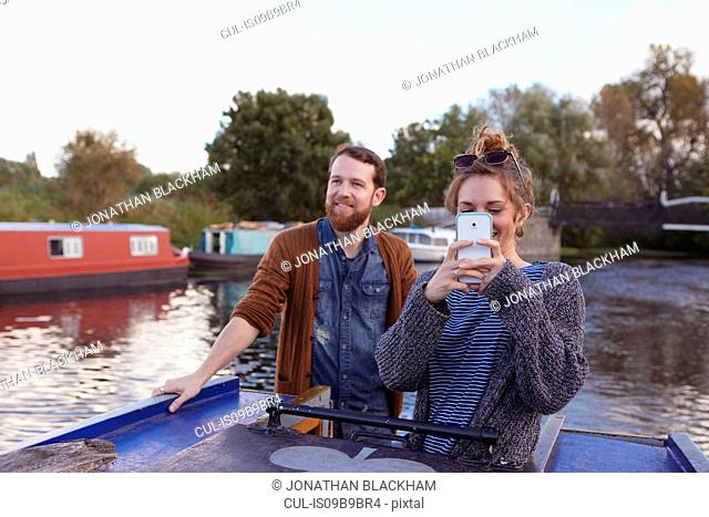 Couple taking photo on canal boat