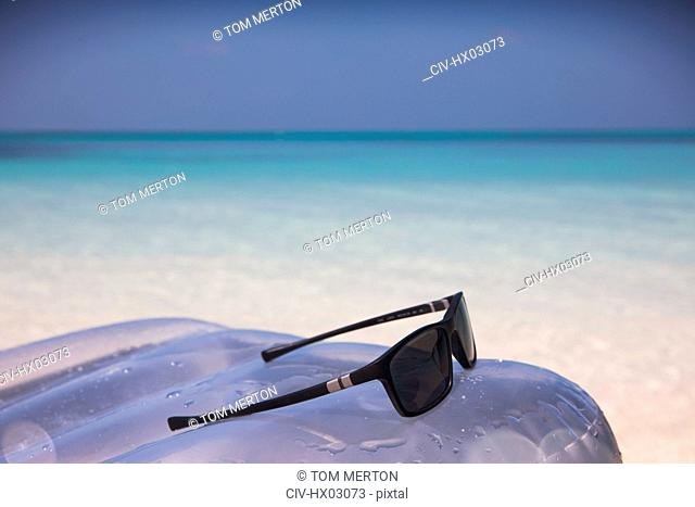 Sunglasses on inflatable raft in tropical blue ocean