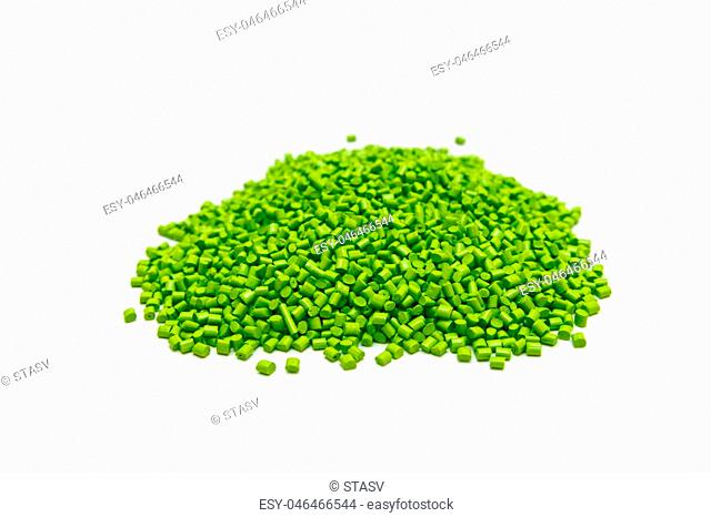 Green plastic pellets on a white background. Polymeric dye for plastics