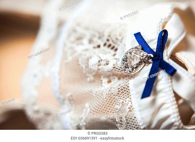 A white linen garter with a blue bow