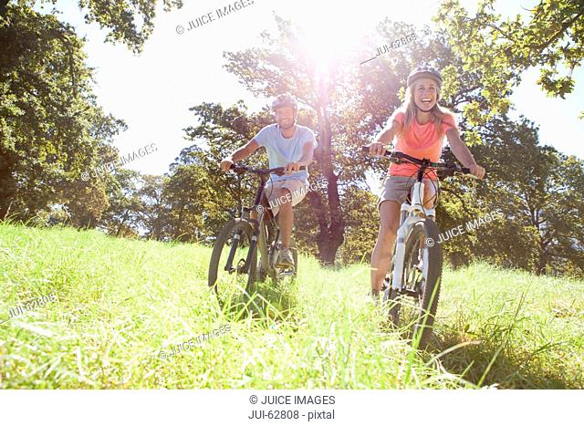 Couple riding mountain bikes in rural field