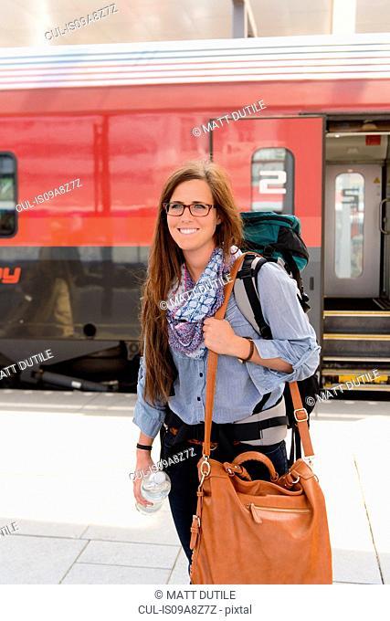 Female backpacker in train station, Salzburg, Austria