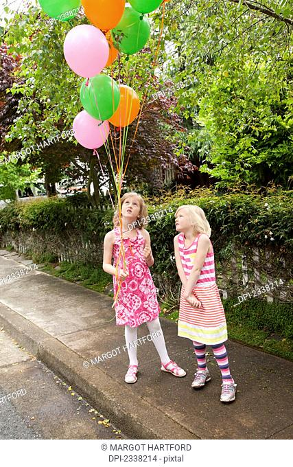 Two young girls standing on a sidewalk with a bouquet of balloons; Pacifica, California, United States of America