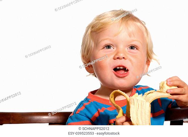 Two year old blond boy posing on a white background