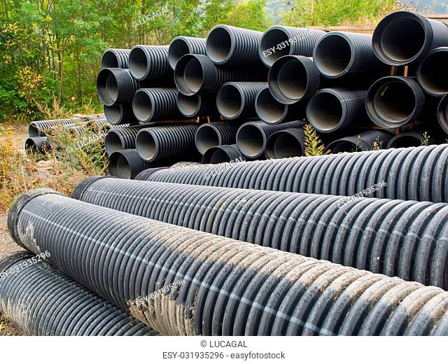 group of big plastic (Polyethylene) corrugated pipes stacked in a construction site