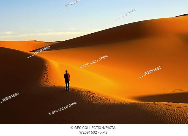 Tourist walking at sunset in the sand dunes of the Erg Muzuruq, Sahara desert, Libya
