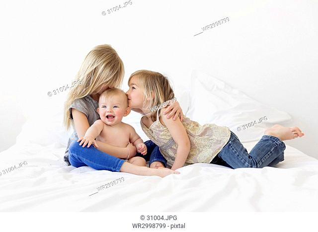 Two blond girls and a baby boy on a bed, girls kissing boy's head