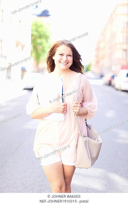 Smiling young woman walking on street