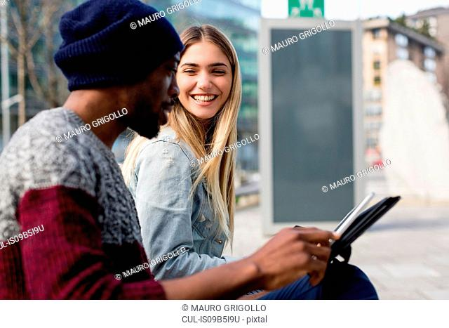Young man and woman sitting outdoors, smiling, man holding digital tablet