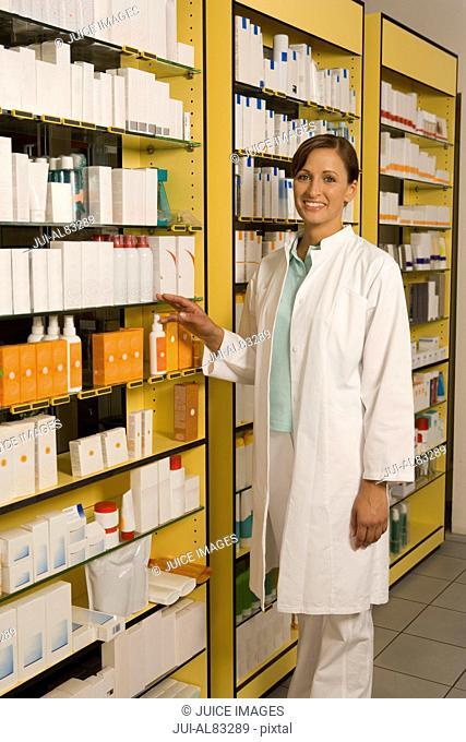 Female pharmacist standing next to shelves of medication