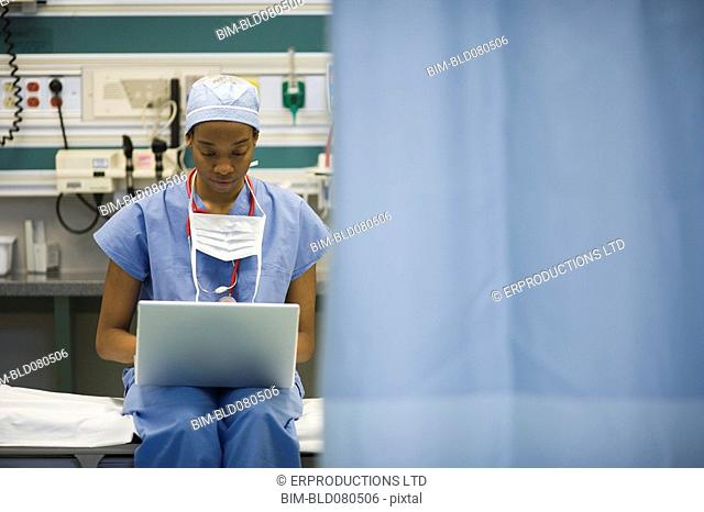 Black surgeon typing on laptop in hospital